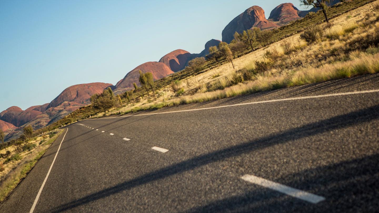 Straße zum Ayers Rock/Uluru im Northern Territory in Australien. traveljunkies Reisen für junge Leute